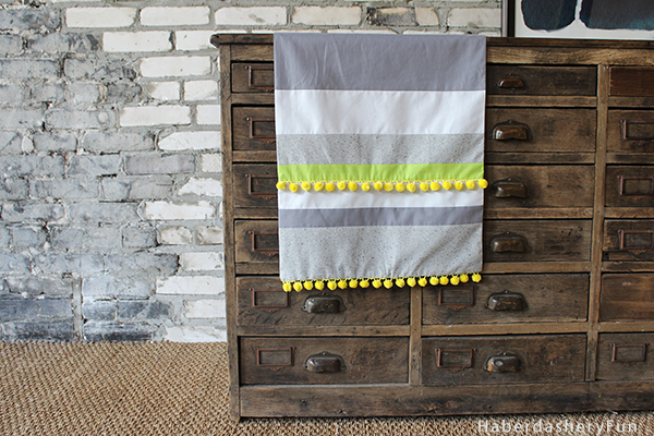 This is a fun and easy tutorial for a table runner with pom pom on the ends. Also a perfect stash buster.  Get more info at HaberdasheryFun and how to sew a colorful pom pom table runner.