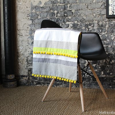 This is a perfect stash buster. Sew a colorful pom pom table runner.